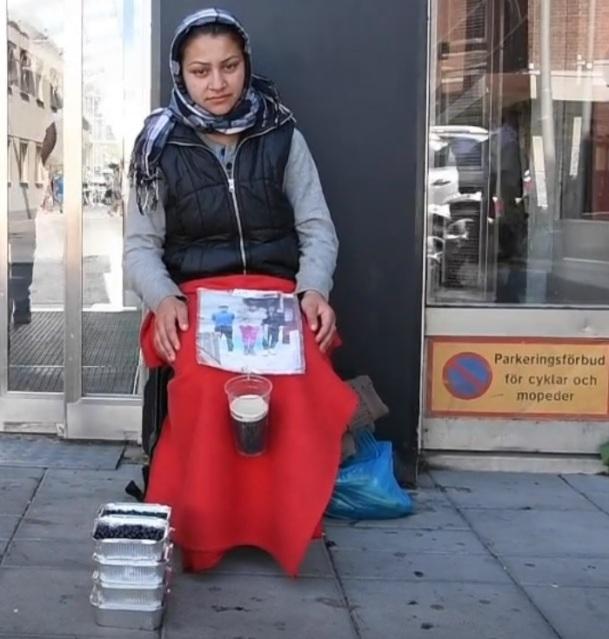 Tiggare i Eskilstuna kringgår krav på tillstånd för att tigga genom att sälja bär. I bilden sitter 22-åriga Maria Narcisa från Rumänien