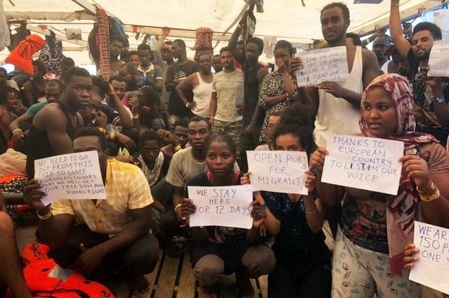 Migranter från Afrika har försetts med lappar av aktivisterna på Open Arms, skrivna av aktivisterna på ett språk de flesta av afrikanerna inte förstår